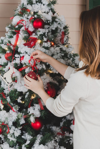 Cropped Image Of Woman Decorating Christmas Tree