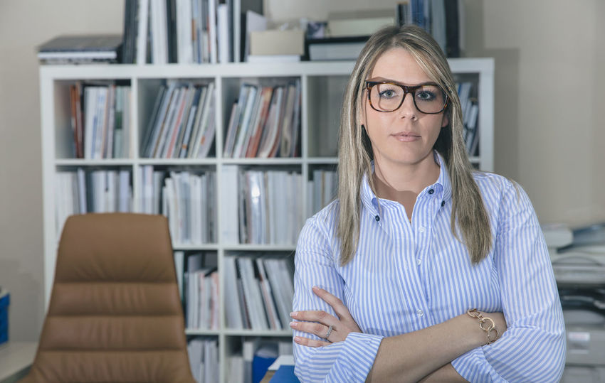 Portrait of young businesswoman with glasses standing in office against of bookcase Business Busy Company Female Power Glasses Horizontal Leader Woman Working Writing Beauty Business Finance And Industry Businesswoman Caucasian Chief Executive  Female Headquarters Job Notebook One Person Portrait Professional Real People Sucess