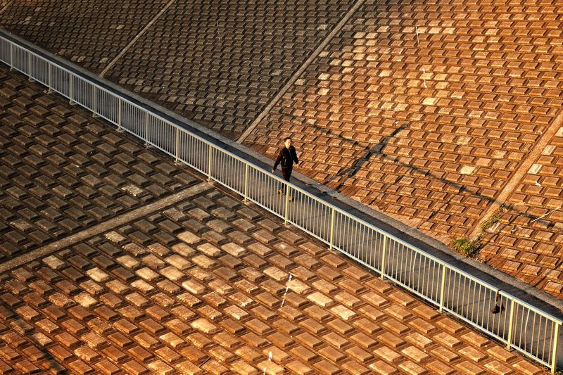 High angle view of man walking on footpath by roof