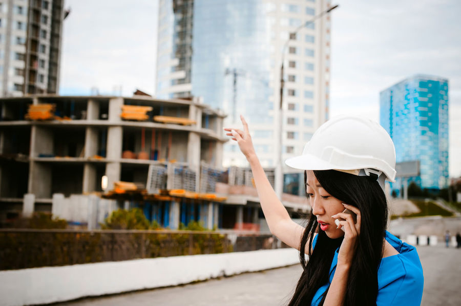 Architecture Building Exterior Built Structure Cap City Construction Site Day Development Hardhat  Headshot Headwear Helmet Helmets Lifestyles Occupation One Person Outdoors People Real People Sky Technology Wireless Technology Women Young Adult Young Women