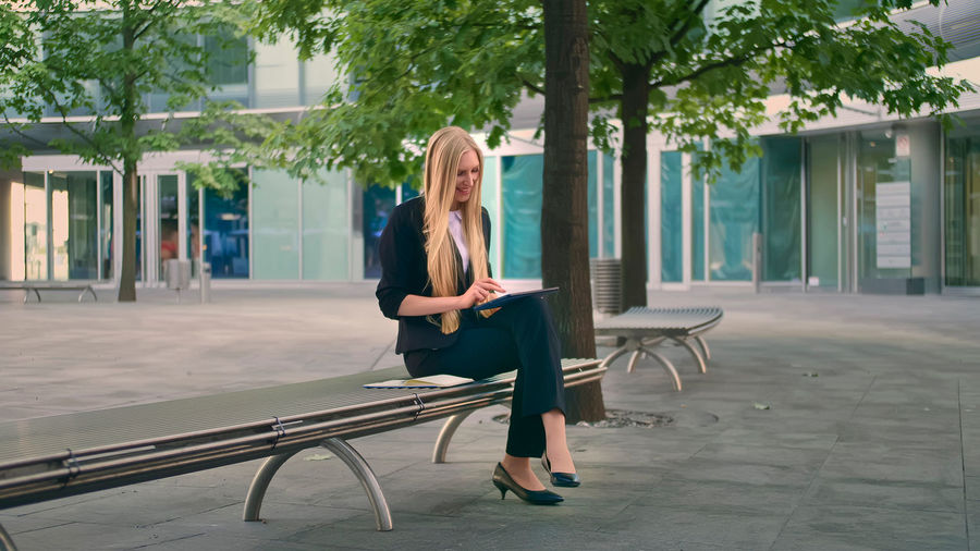 Woman sitting on seat in city