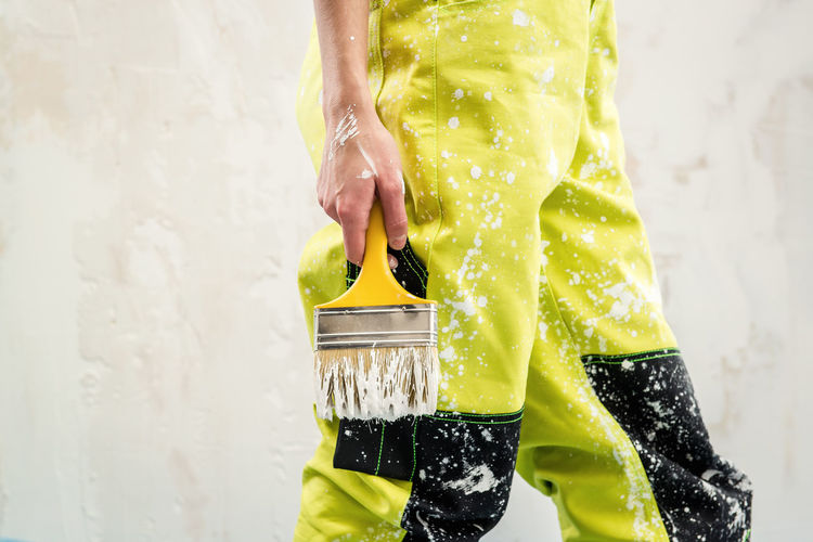 Cropped Image Of Woman Wearing Dirty Coveralls Holding Paintbrush While Standing Against Wall