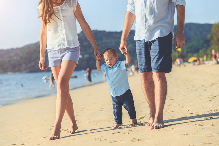 Low section of mother and father walking with son on sand at beach