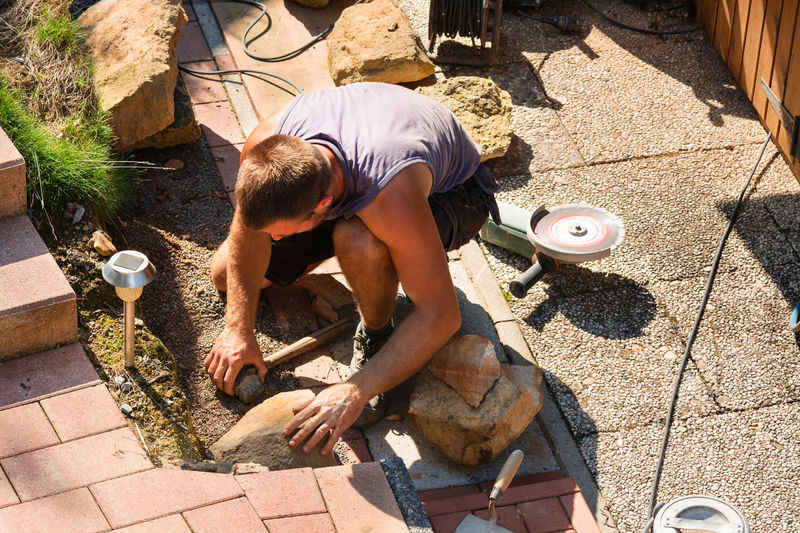 High angle view of manual worker working on footpath during sunny day