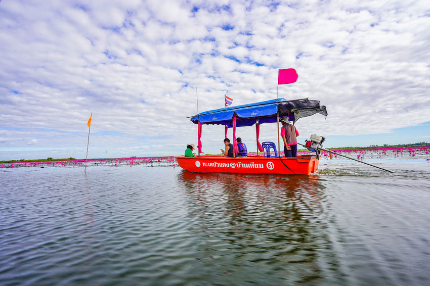 Water Nautical Vessel Sky Sea Cloud - Sky Day Mode Of Transportation Nature Transportation Red Waterfront Group Of People Safety Outdoors Protection Real People Security Beauty In Nature Men Floating On Water Red Lotus In Thailand Red Lotus Lake