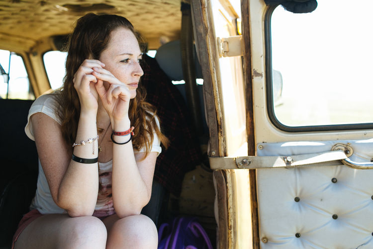 Thoughtful Mid Adult Woman Sitting In Vehicle