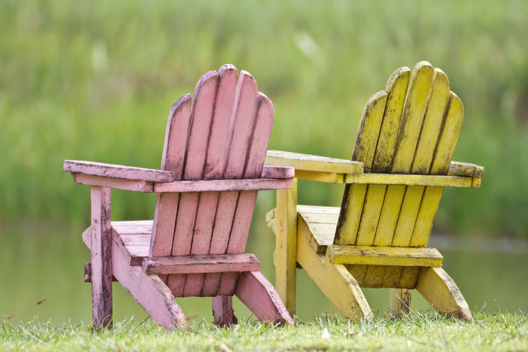 Wooden chairs on field against plants