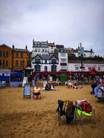 People on beach against buildings in city