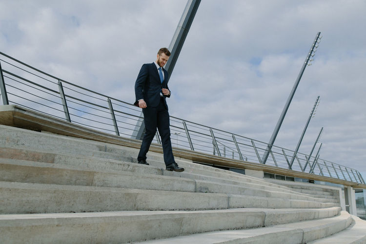 Businessman Walking On Staircase Against Sky