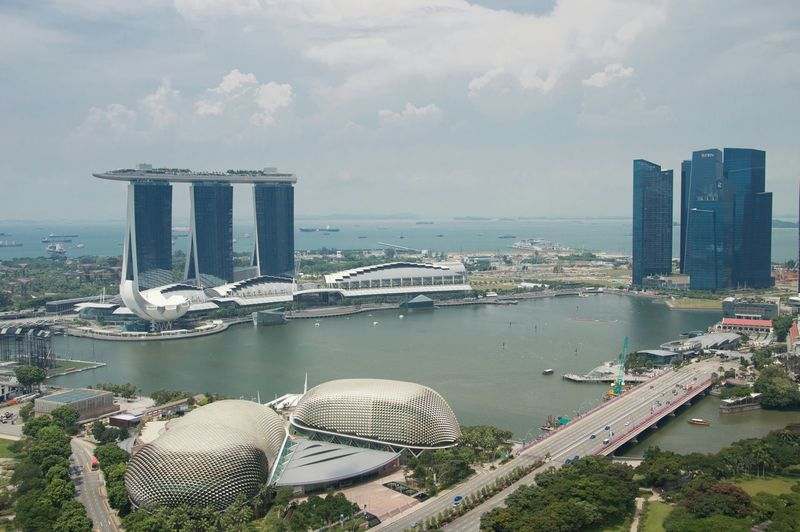 Marina Bay Sands And River Against Cloudy Sky In City