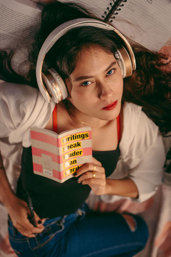 Portrait of young woman holding book at home