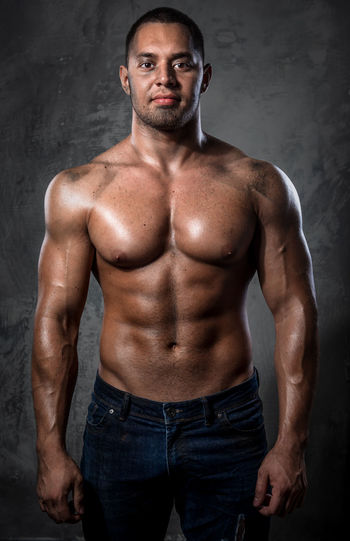 Portrait of shirtless muscular worker standing against wall