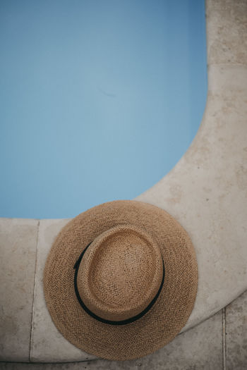 Close-up of hat on table by swimming pool