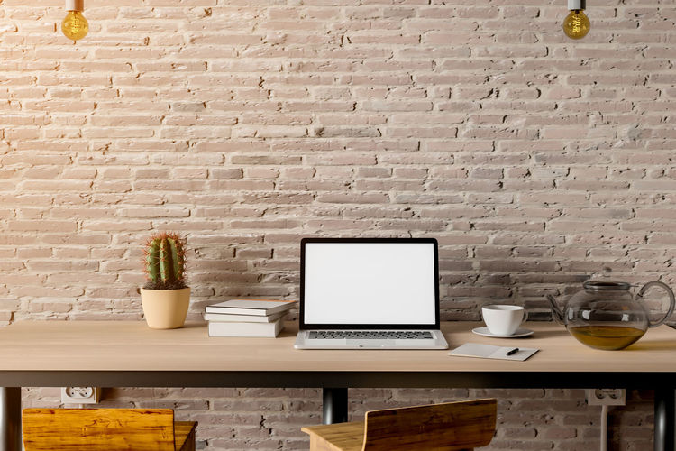 work space Brick Brick Wall Coffee Cup Communication Computer Connection Cup Food And Drink Furniture Indoors  Laptop Mug No People Potted Plant Still Life Table Technology Wall Wall - Building Feature Wireless Technology