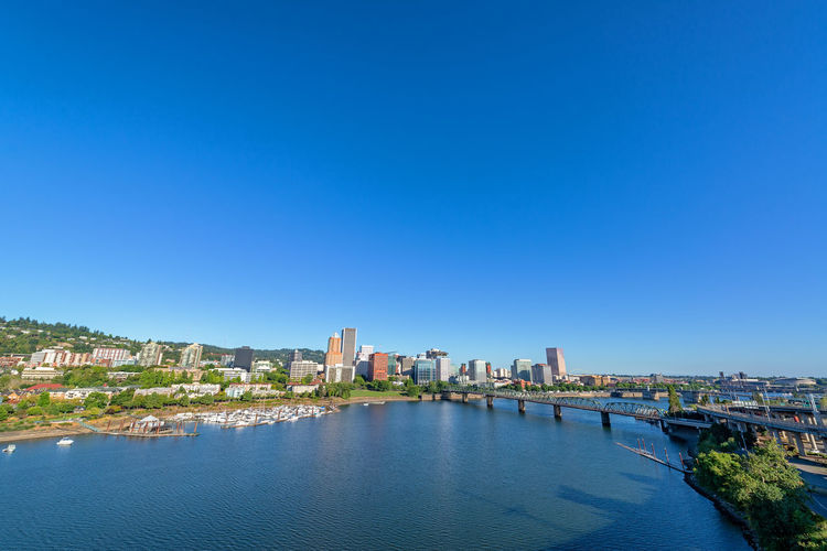 Wide angle view of downtown Portland, Oregon and the Willamette River Portland Oregon No People Outdoors Cityscape Travel Tourism Travel Destinations Building Exterior Built Structure Architecture Sky City Building Nature Office Building Exterior Skyscraper Pacific Northwest  Northwest Willamette River  River Blue Sky Skyline Urban Skyline Urban United States USA Bridge Bridge - Man Made Structure Hawthorne Bridge Marina Water Blue Clear Sky Copy Space Waterfront Day Residential District