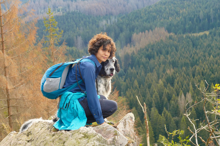 Portrait of a young woman and a dog hiking in the mountains of harz, germany