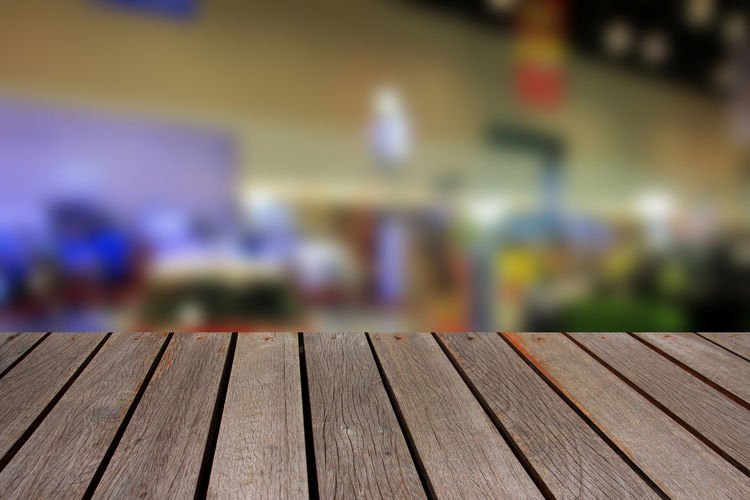 Wooden table and blurred image of motor show,show room,motor expo for background Abstract; Acceleration; Aerial; Auto; Automobile; Automotive; Background; Benz; Blur; Blurred; Bokeh; Business; Car; Color; Concept; Cooper; Crowd; Defocused; Depth; Distribution; Dream; Drive; Exhibition; Exterior; Inside; Interior; Lifestyle; Light; Min Close-up Day Focus On Foreground No People Wood - Material
