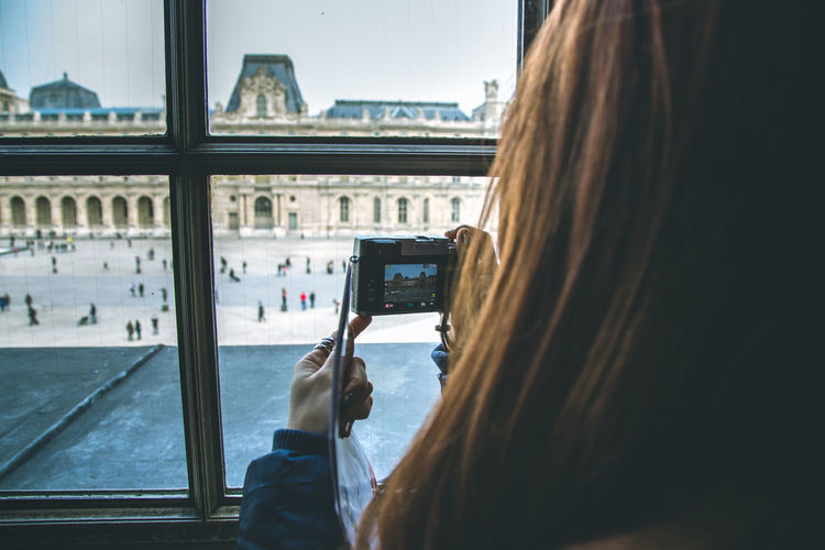 Rear view of woman photographing musee du louvre with camera