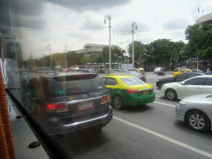 Vehicles on road in city against sky
