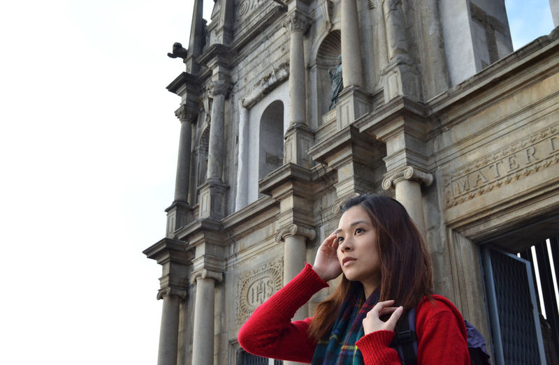Young woman looking away against building
