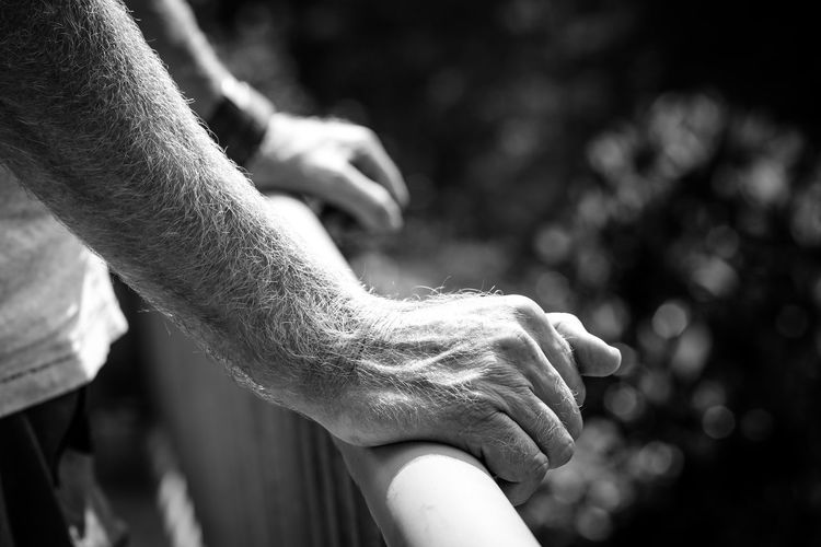 Close-Up Of Man Hand Holding Railing