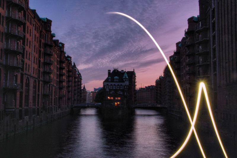 Illuminated Light Painting Over River By Buildings Against Sky In City