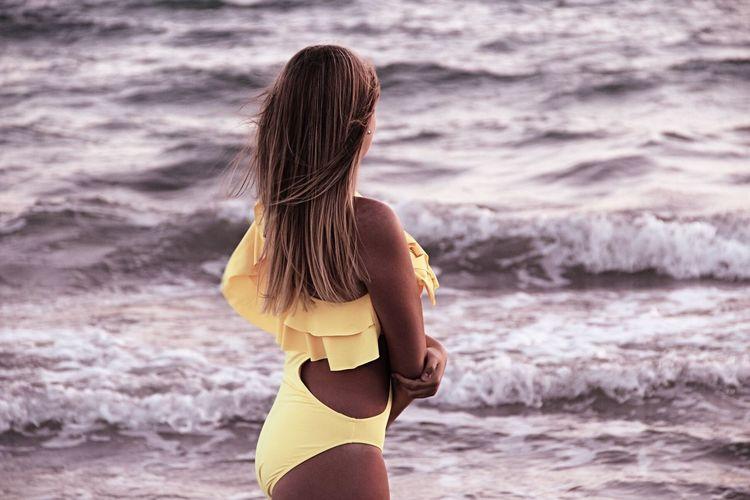 Rear View Of Bikini Woman Standing At Beach