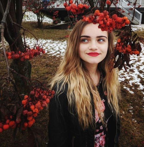 Teenage young woman with red lipstick under a tree with fall foliage, smiling off in the distance