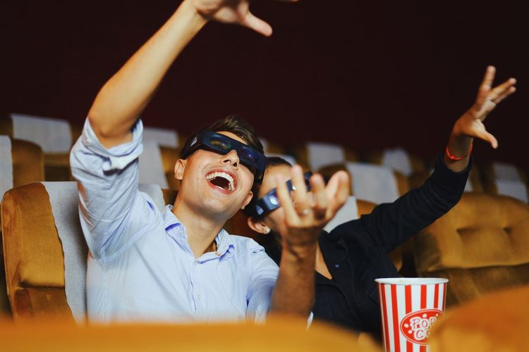 Woman holding food by man gesturing in movie theater
