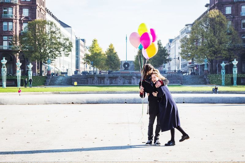 Full Length Of Happy Couple With Balloons In City