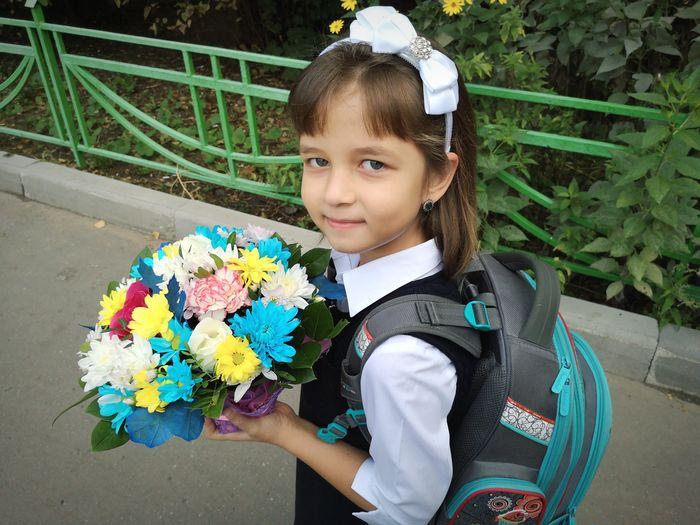 Portrait of girl wearing school uniform holding flowers