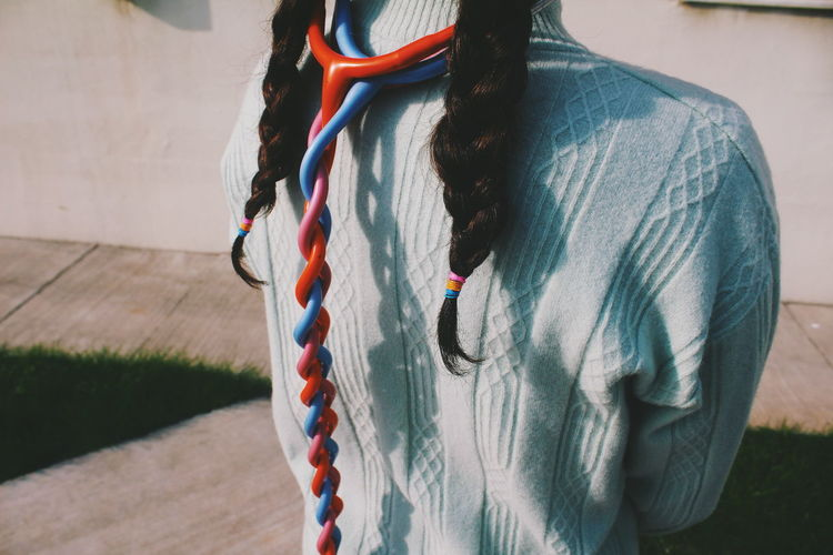 Rear View Of Woman With Braided Hair And Stethoscope Standing Outdoors