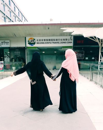 Women in burka holding hands against building