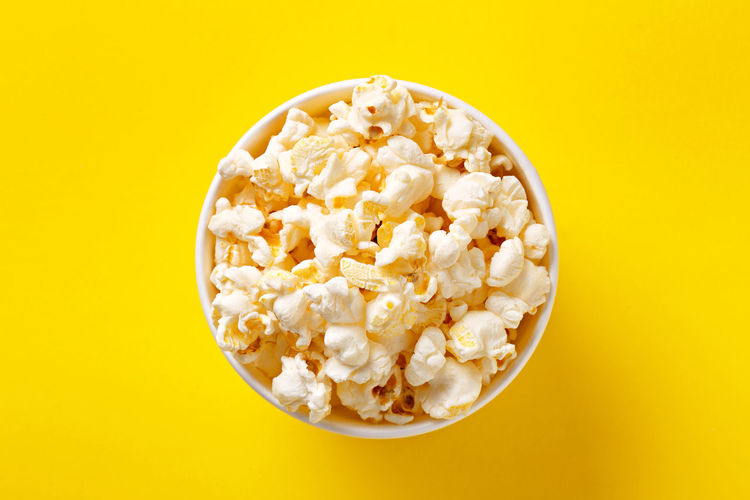 Directly above shot of popcorn against yellow background
