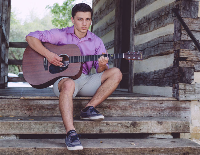 Portrait of man playing acoustic guitar while sitting on steps at log cabin