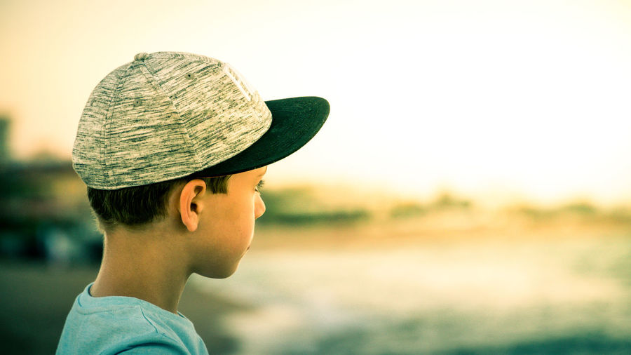Over ths shoulder shot of a young boy wearing a sport cap and looking into the distance Boys Casual Clothing Childhood Clear Sky Close-up Day Elementary Age Focus On Foreground Hat Headshot Leisure Activity Lifestyles Nature One Person Outdoors Real People Side View Sky