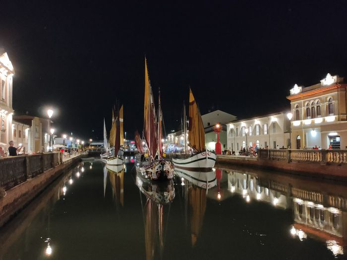Boats moored in canal at night