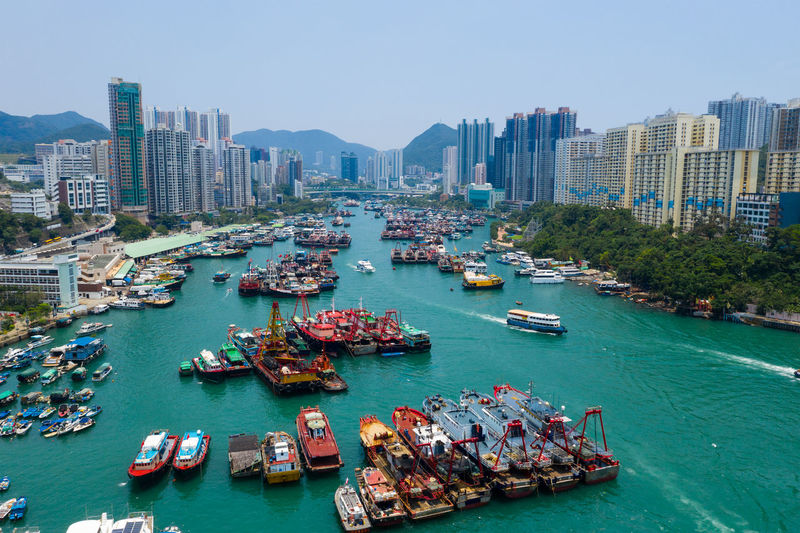 High angle view of boats in river by cityscape against sky