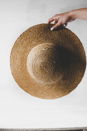 Close-up of hand holding hat over white background