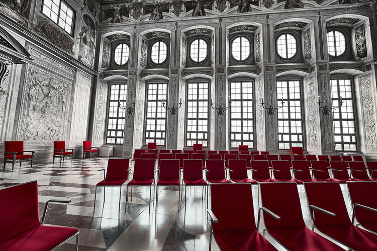 Empty chairs and tables in glass building