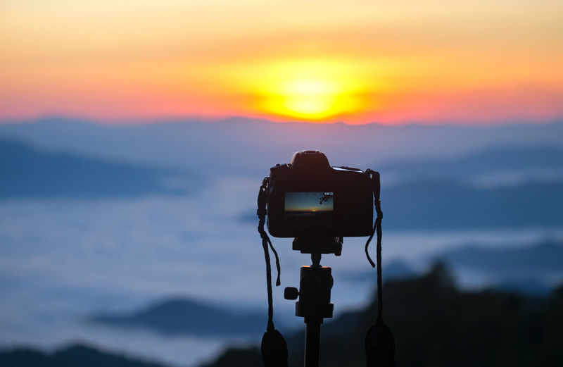 Camera photographing against sky during sunset