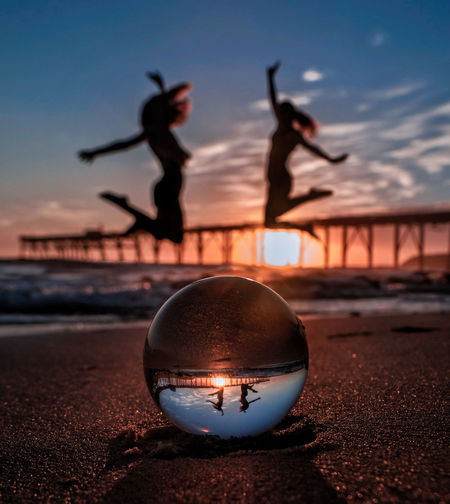 Upside down image of silhouette ball on beach against sky during sunset