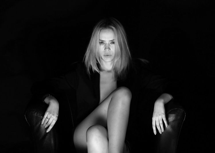Confident woman sitting on chair against black background