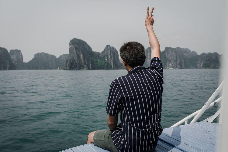 Rear view of man gesturing while sitting in boat at sea against sky