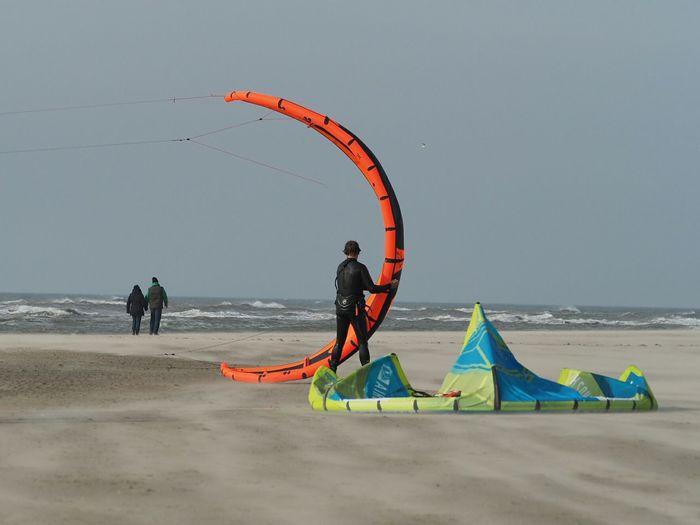 Rear View Of Man Preparing Kiteboard At Beach