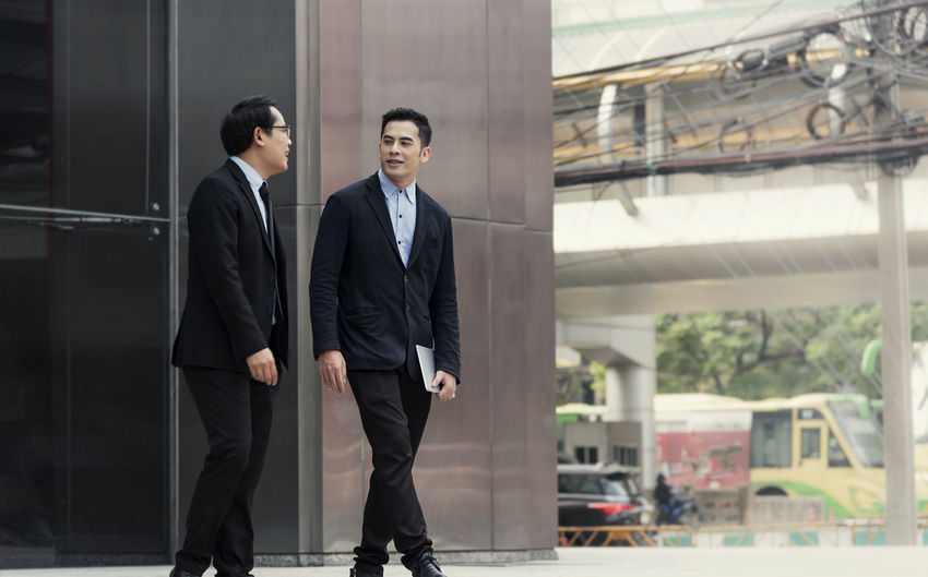 Businessmen discussing while walking in front of office