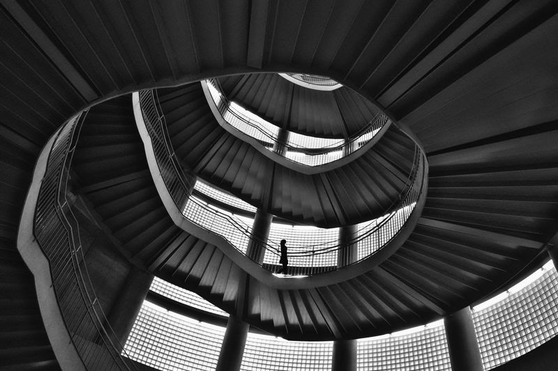 Low Angle View Of Silhouette Woman Standing On Spiral Staircase
