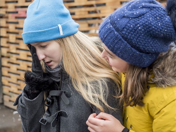 Blond Hair Cap Close-up Cold Temperature Day Friendship Jacket Knit Hat Lifestyles Outdoors Real People Sad Togetherness Two People Warm Clothing Winter