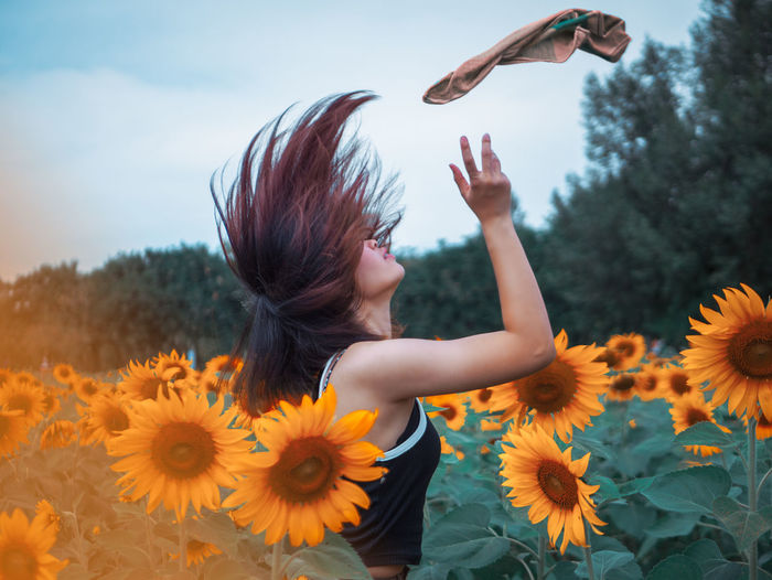 Woman throwing napkin while standing amidst flowering sunflowers