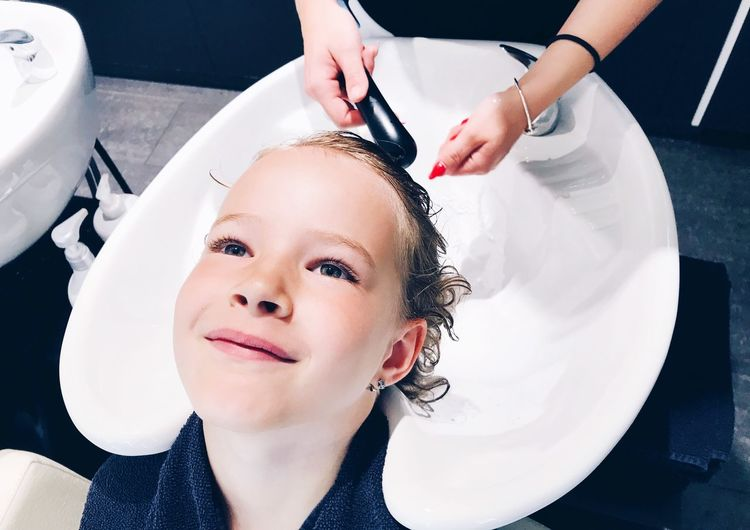 Cropped Hairdresser Washing Hairs Of Girl In Salon